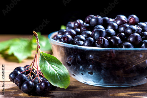 Aronia melanocarpa or black chokeberry in glass bowl on wooden table.Herbalism