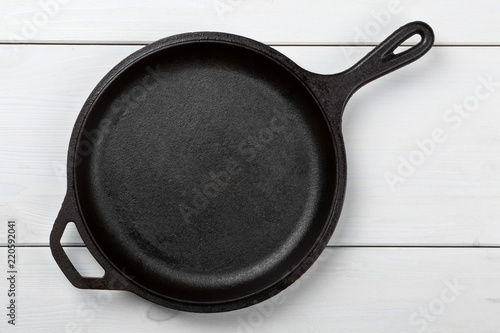 Empty, clean black cast iron pan or dutch oven top view from above on white table
