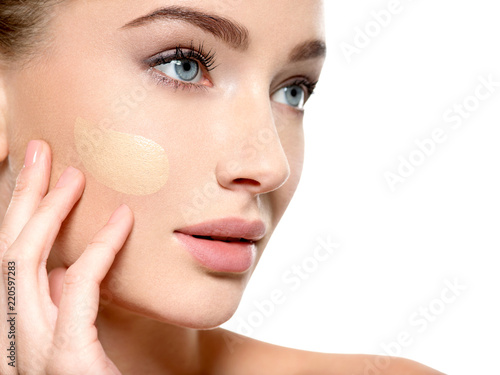 Foto Young woman with cosmetic foundation on skin.