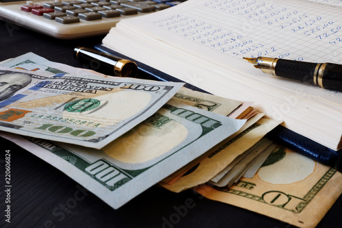 Photo Ledger, calculator and dollar banknotes. Bookkeeping.