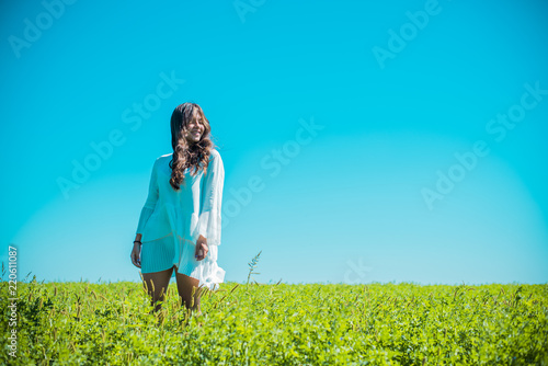 Poster Pony Freedom concept. Young happy woman in green field, evening light. Blue sky behind. Beauty Girl Outdoors enjoying nature. Beautiful Teenage Model girl in white dress running on the meadow