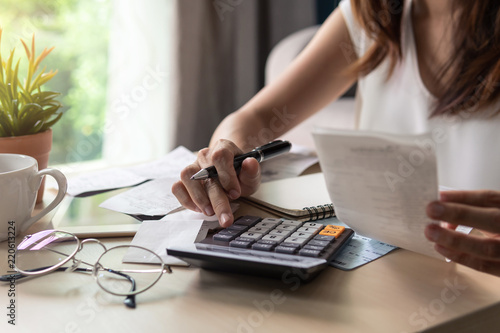 Fototapeta Stressed young woman checking bills, taxes, bank account balance and calculating expenses in the living room at home obraz