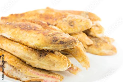 Dish of fried fishes red mullets isolated on white background