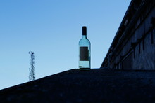 Empty Wine Bottle In Front Of An Old Woodshed