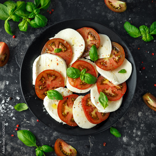 Fotomural Caprese salad with tomatoes, mozzarella cheese and fresh basil leaves in a black plate