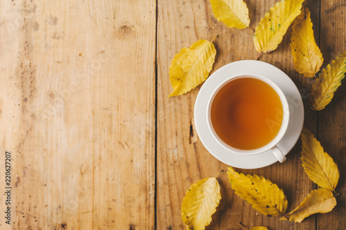 Autumn tea on wooden table with leaves