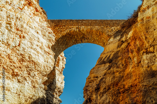 Photo Stone Bridge Over Rock Formations In Lagos, Portugal