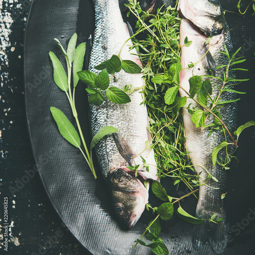 Cooking fish dinner. Flat-lay of raw uncooked sea bass fish with green herbs on dark plate over rustic wooden painted background, top view, square crop. Helathy, clean eating, dieting food concept