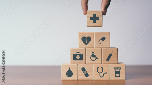 Concept of Insurance for your health, Hand hold wooden block with icon healthcar Canvas
