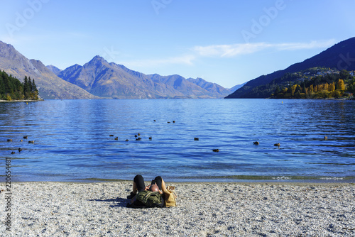 Spoed Foto op Canvas Oceanië Male caucasian using smart phone and relaxing on the beach of Lake Wakatipu , Queenstown , South Island of New Zealand
