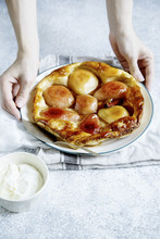 Female Hands Holding Tart Tatin With Pears And Whipped Cream