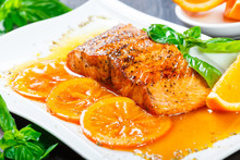 Honey Glazed Fillet Salmon With Orange Slices, Spices And Basil On White Plate On Dark Background. Delicious Dish Of Seafood
