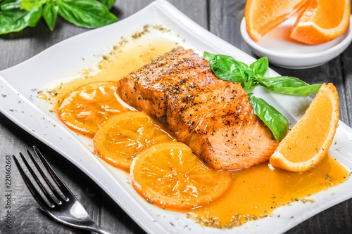 Foto Honey Glazed fillet salmon with orange slices, spices and basil on white plate on dark background