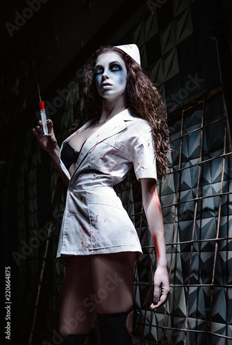 Horror shot: creepy wicked insane nurse (doctor) in bloody uniform, with syringe in hand Wallpaper Mural
