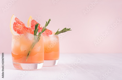 Fototapeta Summer cold cocktail with ice cubes, juice and slices grapefruit on pastel pink background