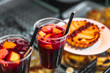Refreshing sangria or compote with fruits stands near cakes
