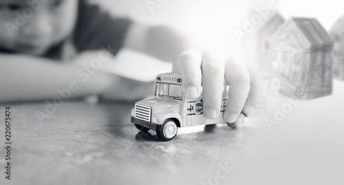 Fotografie, Tablou  Yellow school bus toy model in child's hand