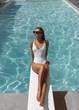 Leinwandbild Motiv Gorgeous girl enjoys relaxing at the luxurious pool