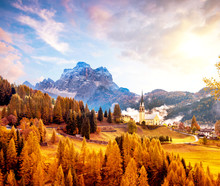 Amazing Magical Autumn Unbeatable Landscape With The Church And  Yellow Larch On A Background Of Mountains In The Dolomites In A Sunny Day Near Codalonga, Alps, Italy.
