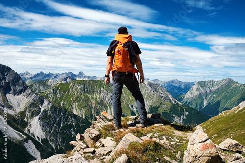 Photo Mann genießt die Aussicht auf die Alpen vom Gipfel eines Berges