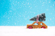 Toy car with Christmas tree in snowy winter