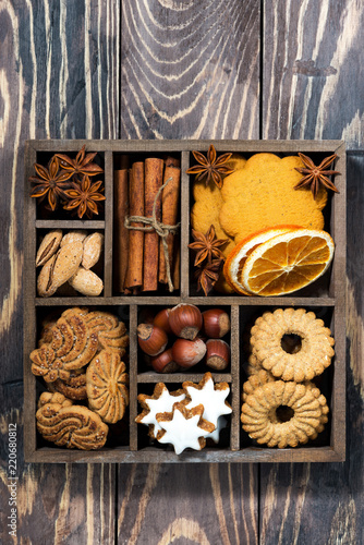 wooden box with Christmas sweets and spices on wooden background, vertical top view