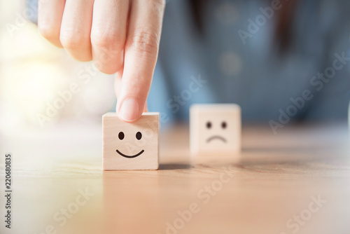 Fotografie, Obraz  Close up customer hand choose smiley face and blurred sad face icon on wood cube, Service rating, satisfaction concept