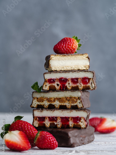 Cakes and wafers covered with chocolate and strawberries