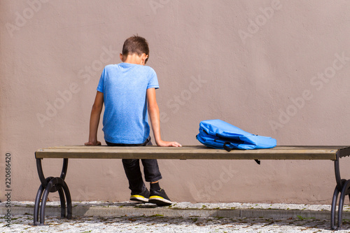 Murais de parede Sad, tired child sitting alone on the bench outdoors.