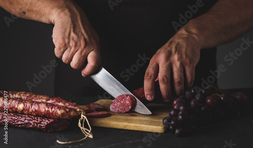 Men's hands cut sausage salami on a cutting board.