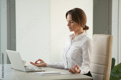 Leinwand Poster Calm mindful businesswoman meditating at office desk with eyes closed, female ex
