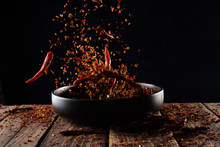 Pouring Cayenne Pepper Powder Into The Bowl On Wood Table,Motion Blur