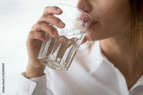 Fotografie, Obraz  Dehydrated woman feeling thirsty holding glass drinking filtered pure mineral fr