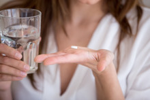 Woman Holding Pill And Glass Of Water In Hands Taking Emergency Medicine, Supplements Or Antibiotic Antidepressant Painkiller Medication To Relieve Pain, Meds Side Effects Concept, Close Up View