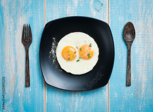 Fried eggs in a plate on a table,top view