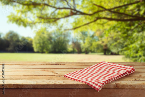 Fototapeta Empty wooden table with tablecloth over autumn nature park background obraz