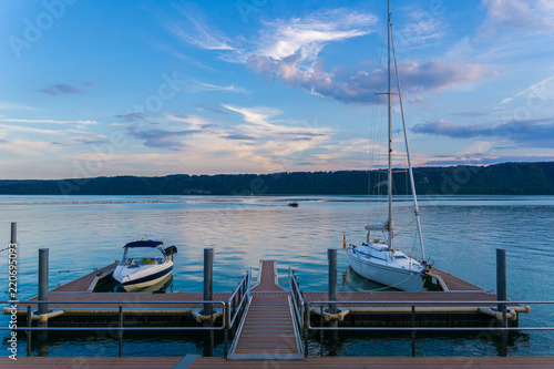 Fotografía  Two boats at landing stage on silent water in twilight atmosphere
