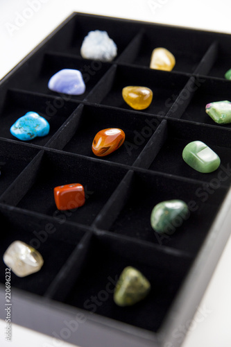 Fotografía  Variety of colorful semi precious stones crystals in organizer box sorted by color isolated on black