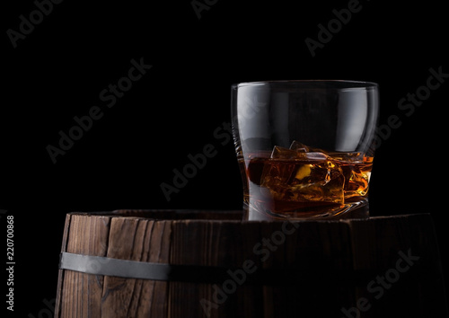 Glass of whiskey with ice cubes on top of wooden barrel. Cognac brandy drink