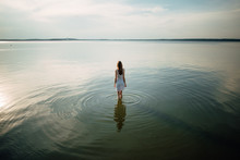 Woman In Summer Dress Standing On Seashore And Looking At Horizon. Young Beautiful Girl Standing In Water