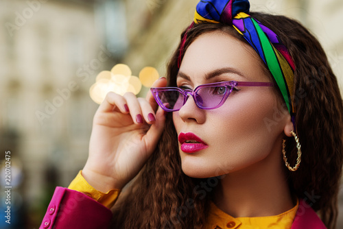 Outdoor close up fashion portrait of young beautiful woman wearing trendy violet sunglasses, colorful headband, circle earrings, posing in street of european city. Copy, empty space for text