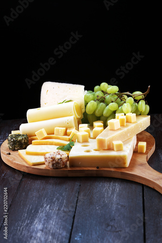 Cheese platter with different cheese and grapes.