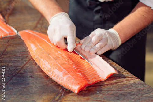 Photographie The chef cuts the salmon on the table.