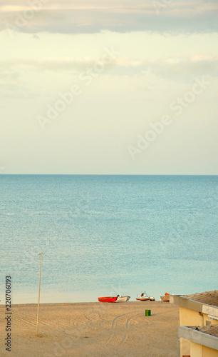 Obraz na plátně  Sandy beach Ionian Sea, southern Italy city Bova Marina, on the shore of the red fishing boat