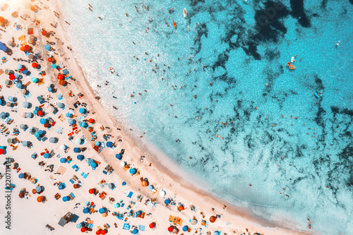 Aerial view of sandy beach with colorful umbrellas, swimming people in sea bay with transparent blue water at sunset in summer. Travel in Mallorca, Balearic islands, Spain. Top view. Landscape