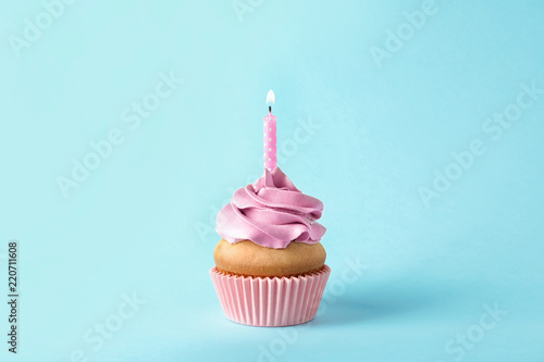 Photo  Delicious birthday cupcake with candle on color background