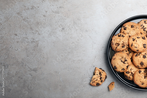 Plate with chocolate cookies and space for text on gray background, top view