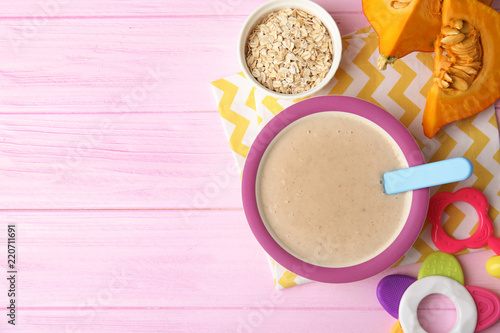 Flat lay composition with plate of healthy baby food and space for text on color background