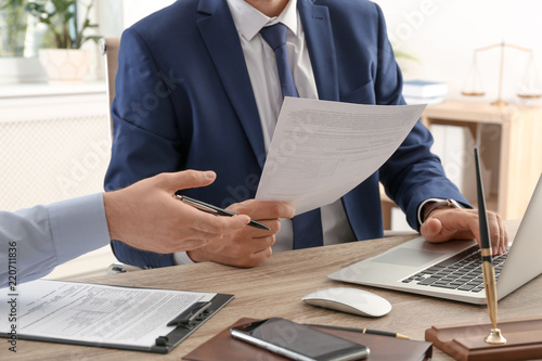 Photo  Lawyer working with client at table in office, focus on hands