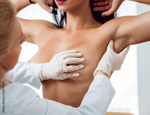 Fototapeta Doctor get examining breast of young woman